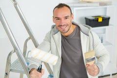 Trabajador en escalera con el rodillo imagen de archivo libre de regalías