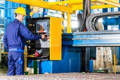 Trabajador en fábrica en el panel de control de la máquina