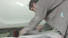 Trabajador en Grey Uniform Polishes Car Door con la herramienta especial almacen de video