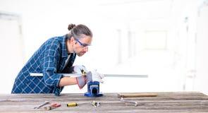 Trabajador en la camisa azul que trabaja con el metal fotos de archivo