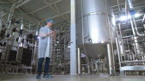 Trabajador en la cervecería cerca de los tanques, tubería que trabaja con la tableta