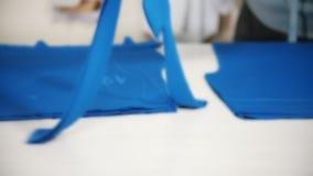 Trabajador en la fábrica que corta el paño azul usando el instrumento especial que sigue las marcas Blured metrajes