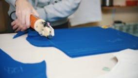 Trabajador en la fábrica que corta el paño azul usando el instrumento especial que sigue las marcas Blured Cámara lenta almacen de metraje de vídeo