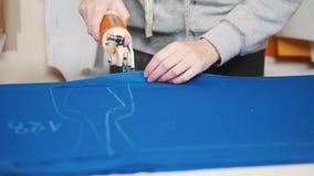 Trabajador en la fábrica que corta el paño azul usando el instrumento especial que sigue las marcas Cierre para arriba metrajes