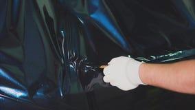 Trabajador en la gasolinera que alisa la película del vinilo por el secador de pelo de la construcción almacen de metraje de vídeo