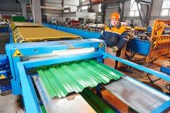 Trabajador en la hoja de metal que perfila la fábrica Imagen de archivo libre de regalías