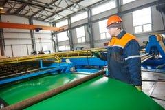 Trabajador en la hoja de metal que perfila la fábrica Imagenes de archivo