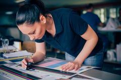 Trabajador en la impresión y aplicaciones centar de la prensa una lupa Imagen de archivo libre de regalías