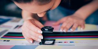 Trabajador en la impresión y aplicaciones centar de la prensa una lupa