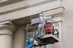 Trabajador en la plataforma que lava un edificio Imagen de archivo