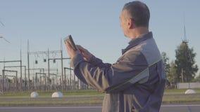 Trabajador en la subestación eléctrica Trabajador con la tableta y el tablero en la reunión en la subestación eléctrica almacen de metraje de vídeo