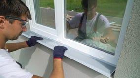 Trabajador en las gafas de seguridad y los guantes protectores que instalan el travesaño del metal en marco de ventana externo de metrajes
