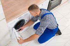 Trabajador en lavadora total de la fijación fotografía de archivo
