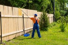 Trabajador en los guardapolvos azules, la camiseta anaranjada, el casquillo y los guantes pintando una cerca de madera Foto de archivo