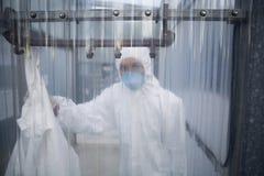 Trabajador en máscara protectora y traje detrás de la pared plástica en el laboratorio Imagen de archivo libre de regalías