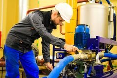 Trabajador en planta industrial usando limpiador del aceite del poder fotografía de archivo