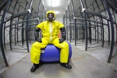 Trabajador en seguridad - uniforme protector, sentándose en barril azul fotografía de archivo