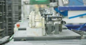 Trabajador en una cadena de producción de las piezas para la industria del automóvil metrajes