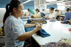Trabajador en una fábrica china de la ropa Fotos de archivo libres de regalías