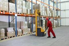 Trabajador en uniforme rojo en el trabajo en almacén