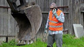 Trabajador enojado que habla con el teléfono elegante cerca de la cucharada del excavador del tractor almacen de video