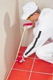 Trabajador envuelto con los azulejos del rojo de la cinta adhesiva Fotografía de archivo