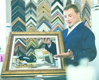 Trabajador feliz que lleva a cabo moldear que enmarca de la imagen de madera Fotos de archivo libres de regalías