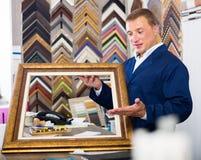 Trabajador feliz que lleva a cabo moldear que enmarca de la imagen de madera Imagen de archivo