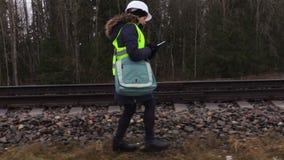 Trabajador ferroviario de sexo femenino que camina a lo largo de ferrocarril almacen de metraje de vídeo