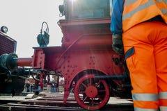 Trabajador ferroviario en la acción con el tren del vapor en fondo Fotos de archivo
