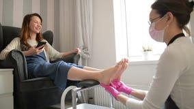 Trabajador fuerte del sal?n Amo concentrado en los guantes de goma rosados que procesan las piernas con el curado de masaje en be almacen de metraje de vídeo
