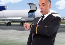 Trabajador hermoso de la línea aérea que mira su reloj Imágenes de archivo libres de regalías