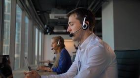 Trabajador hermoso en auriculares que llama a los cuctomers en centro de atención telefónica de la oficina de negocios metrajes