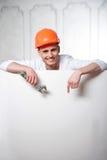 Trabajador hermoso joven detrás del tablero en blanco Imagen de archivo libre de regalías