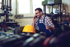 Trabajador hermoso que habla en el teléfono con sus compañeros de trabajo imágenes de archivo libres de regalías