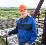 Trabajador hermoso que se coloca para la plataforma de la mucha altitud Imagen de archivo libre de regalías