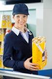 Trabajador hermoso que sostiene las palomitas en el cine Foto de archivo