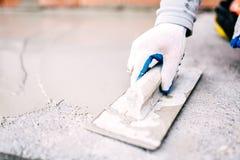 Trabajador industrial en el emplazamiento de la obra que pone el sellante para el cemento de impermeabilización fotografía de archivo