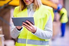 Trabajador irreconocible del almacén de la mujer con la tableta Imagen de archivo