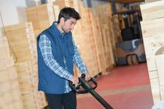 Trabajador joven del almacén que usa el pallettruck para asir la plataforma Imagen de archivo libre de regalías