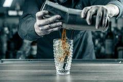Trabajador joven del camarero en el escritorio del camarero en la barra del restaurante que prepara el coctail imagen de archivo libre de regalías