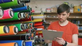 Trabajador joven en almacén con el tablero que comprueba inventario El hombre trabaja en el departamento de ventas de materiales  almacen de metraje de vídeo