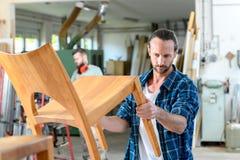 Trabajador joven en el taller de un carpintero con la silla de madera fotos de archivo