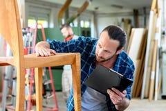 Trabajador joven en el taller de un carpintero con la silla de madera foto de archivo