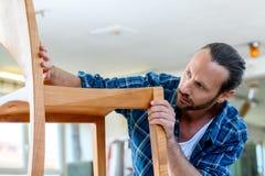 Trabajador joven en el taller de un carpintero con la silla de madera fotografía de archivo