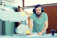 Trabajador joven en el taller de un carpintero usando la sierra fotos de archivo libres de regalías