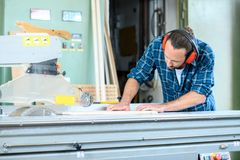Trabajador joven en el taller de un carpintero usando la sierra imagen de archivo