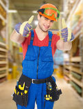 Trabajador joven profesional con los pulgares para arriba en la tienda Imagenes de archivo