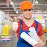 Trabajador joven profesional con los pulgares para arriba en la tienda Foto de archivo