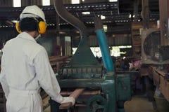 Trabajador joven profesional en el trabajo uniforme de la seguridad blanca con la máquina del planeamiento en fábrica imagenes de archivo